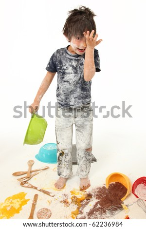 Adorable 7 year old boy making mess baking cookies. - stock photo