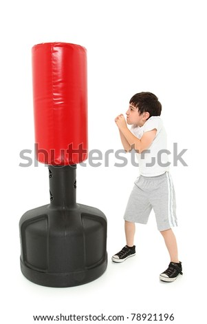 Adorable 8 year old boy practicing punches with a free standing heavy bag over white. - stock photo