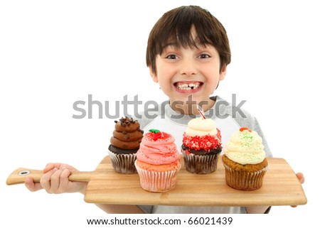 Adorable 7 year old boy smiling with tray of cupcakes.  Strawberry, chocolate, carrot cake, peppermint.
