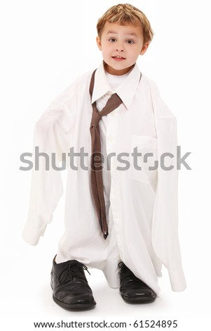 Adorable 4 year old caucasian boy in over sized shirt and tie over white. - stock photo
