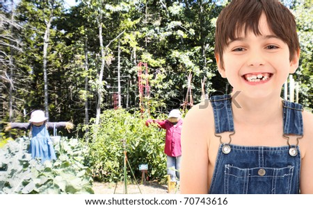 Adorable 7 year old farm boy in overalls in organic garden with scarecrows. - stock photo