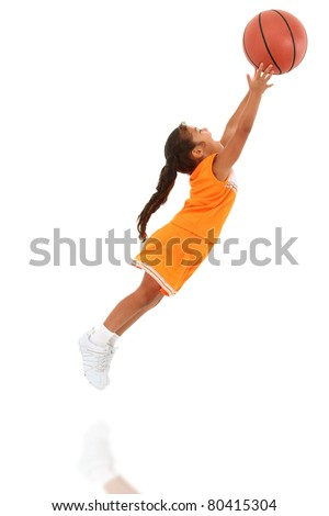 Adorable 5 year old girl child in orange sport team uniform jumping for basketball over white background. - stock photo