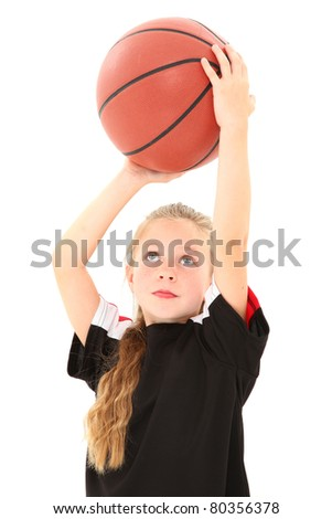 Adorable 5 year old girl child making free throw with basketball in uniform over white background. - stock photo