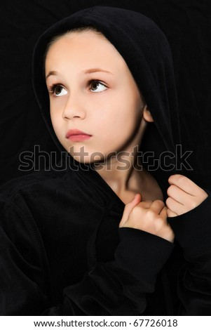 Adorable 7 year old girl in black looking to side with worried or scared expression. - stock photo
