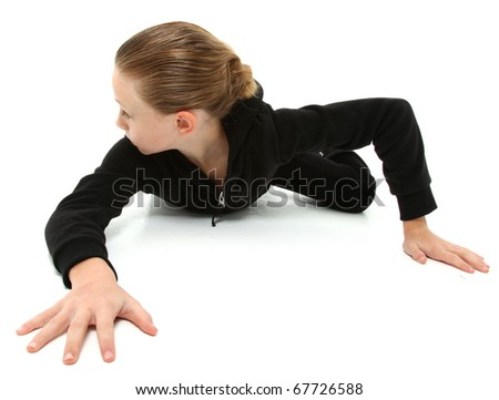 Adorable 7 year old girl in black suit crawling and looking behind on white floor. - stock photo