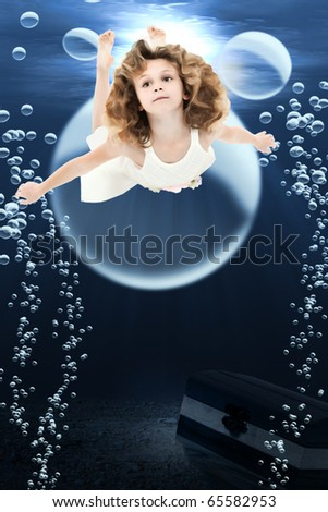 Adorable 7 year old girl in dress swimming under ocean swimming past treasure chest and bubbles. - stock photo