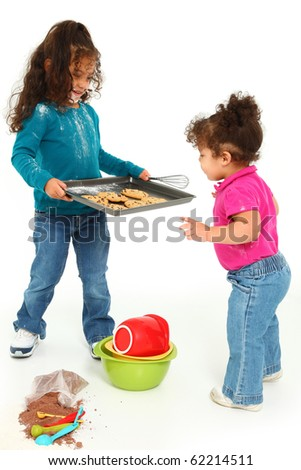 Adorable 3 year old Hispanic-African American girl, baking cookies over white background.  Giving cookies to little sister. - stock photo