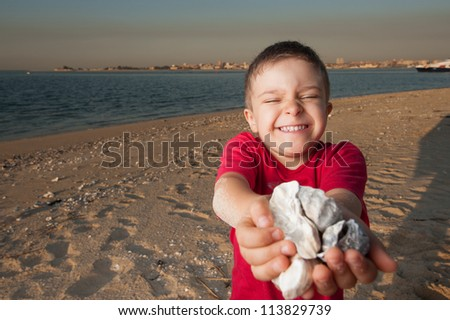 adorable 5 year old kid playing with some shells near the river bank - stock photo