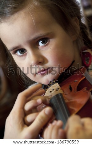Adorable 3 year old little girl learning  playing violin on music school class. First steps. - stock photo