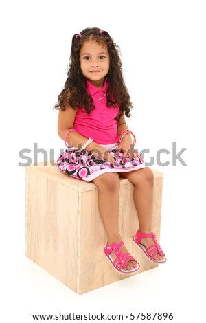 Adorable 3 year old mixed race girl sitting on wooden box over white background. - stock photo