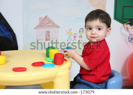 Adorable 2 year old preschooler boy child sitting at table playing with molding clay dough. - stock photo