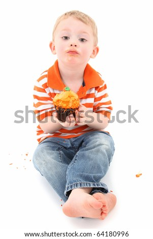 Adorable 2 year old toddler boy with orange frosting cupcake over white background. - stock photo