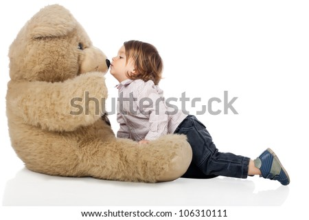 Adorable 2 years old boy wearing shirt and jeans kissing and playing with a big stuffed plush bear. High resolution image isolated on white background with copy space. Studio shot