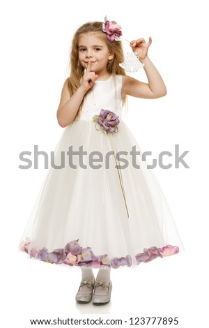 Adorable 6 years old girl in princess dress holding bells with finger on lips, over white background - stock photo