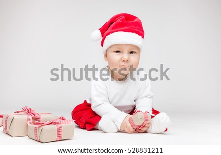 Adorable young baby boy wearing a Santa hat opening Christmas presents