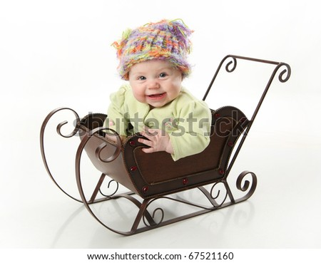 Adorable young baby girl wearing a knit stocking cap sitting in a metal Christmas snow sleigh - stock photo