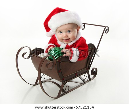 Adorable young baby wearing a santa claus suit and hat sitting in a metal Christmas snow sleigh holding an ornament - stock photo