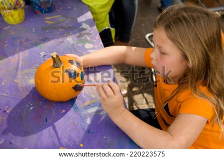 Adorable young blond girl painting a pumpkin for Halloween