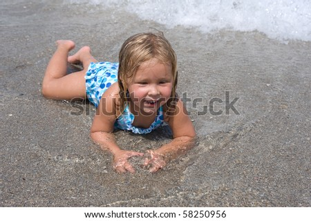 Adorable young blond girl playing in the sand at the beach - stock photo