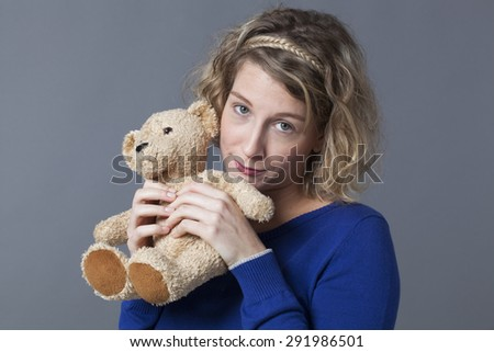 adorable young blonde woman hugging her teddy bear with tenderness for adult innocence - stock photo