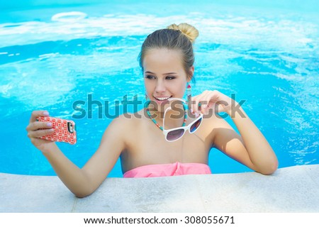Adorable young blonde woman taking selfie in the swimming pool - stock photo