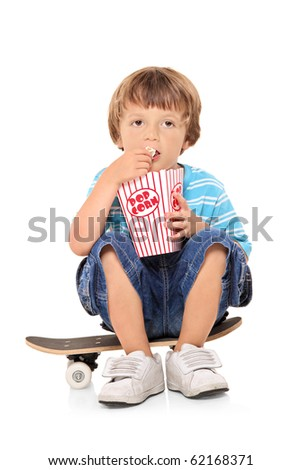 Adorable young boy sitting on a skateboard and eating popcorn isolated against white background - stock photo