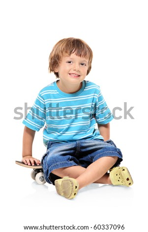 Adorable young boy sitting on a skateboard isolated against white background - stock photo