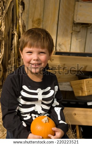 Adorable young brunette boy holding a small pumpkin for Halloween  - stock photo