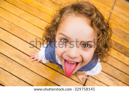 Adorable young brunette girl standing on wooden surface looking upwards into camera, shot from above. - stock photo