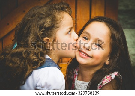 Adorable young brunette girls kissing on cheek, showing love and friendship. - stock photo