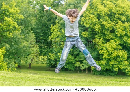 Adorable young child boy in the park. On warm summer day during school holidays. Kid boy jumping and smiling. - stock photo