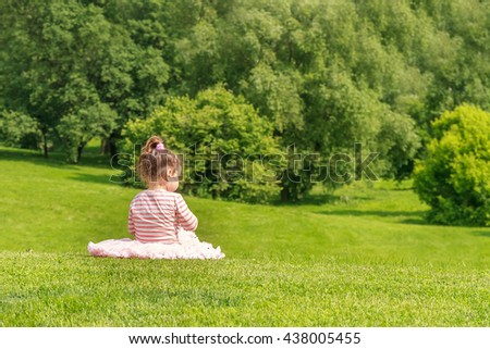 Adorable young child girl in the park. On warm summer day during school holidays. Kid boy dreaming and smiling. - stock photo
