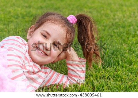 Adorable young child girl in the park. On warm summer day during school holidays. Kid  dreaming and smiling. - stock photo