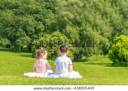 Adorable young child girls, sisters, in the park. On warm summer day during school holidays. Kid  dreaming and smiling. - stock photo