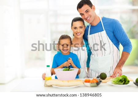 adorable young family cooking in kitchen at home - stock photo