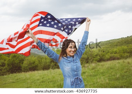 Adorable young girl having enjoyable independence day in cloudy summertime outdoors.