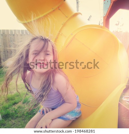 Adorable young girl having fun on slide - Instagram effect - stock photo