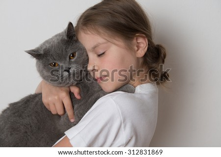 Adorable young girl hold her lovely gray short hair British cat - stock photo