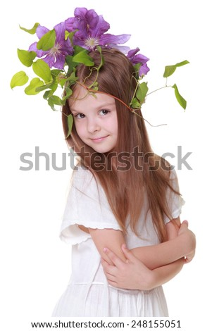 Adorable young girl in a white dress with a beautiful hairstyle of the purple clematis with green leaves isolated on white - stock photo