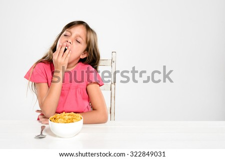 Adorable young girl is sleepy and yawns at the breakfast table with a bowl of nutritious healthy cornflake cereal - stock photo