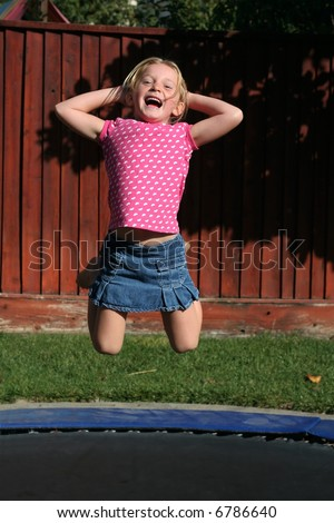 adorable young girl jumping on trampoline