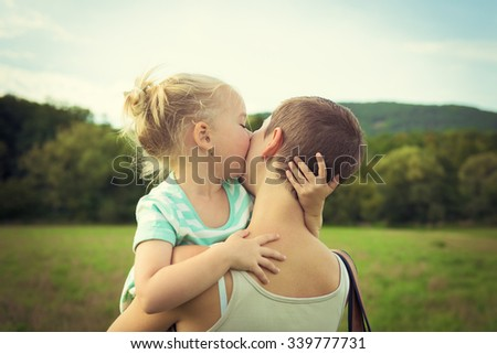 Adorable young girl kissing her mother - stock photo