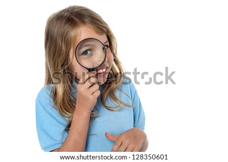 Adorable young girl looking through a magnifying glass, white background. - stock photo