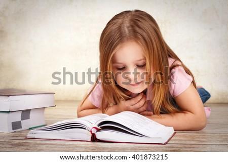 Adorable young girl reading a book - stock photo