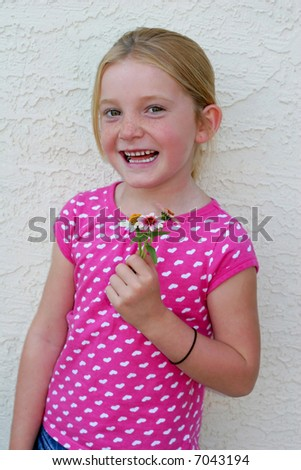adorable young girl smiling and smelling flowers