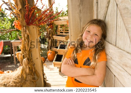 Adorable young girl wearing a jack o' lantern shirt outdoors for Halloween  - stock photo