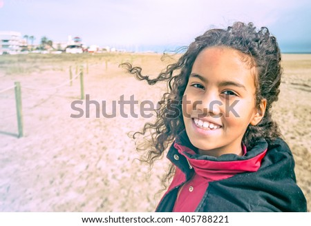 Adorable young girl wearing red coat on sunny beach in Spain.  Beautiful brazilian child with curly hair enjoying wind and sun outside, image for children concept blog. Toned filter lens flare effect - stock photo