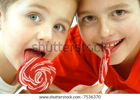Adorable young kids enjoying lollipops together; isolated on white - stock photo