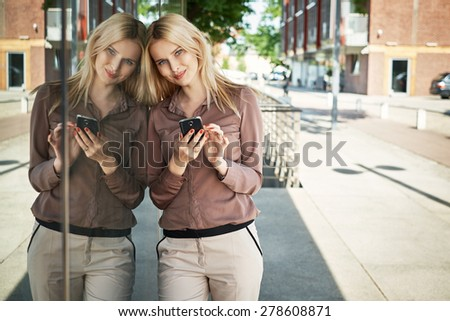 Adorable young lady using the cellphone - stock photo
