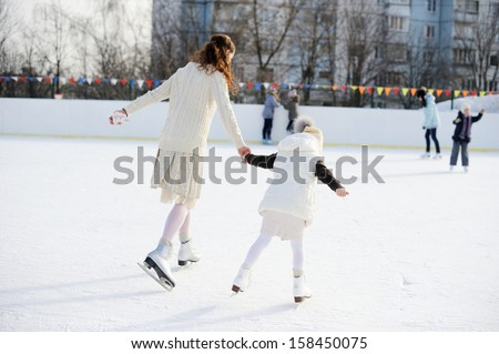 Adorable young mother with her daughter in white clothes on the ice rink - stock photo